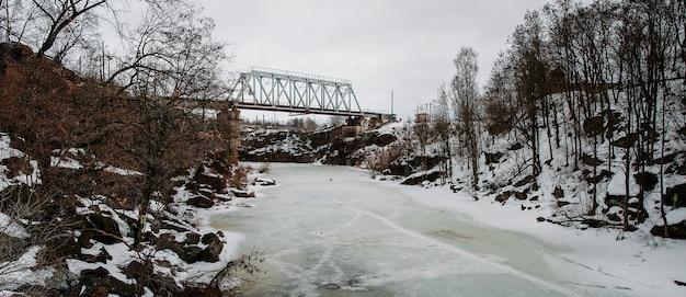 Metalowy most, kolej przez rzekę. zimowa lodowa rzeka, piękny śnieżny krajobraz z zamarzniętym jeziorem. pokryta śniegiem potok w górach. widok z góry, naturalny. las i kamienie.