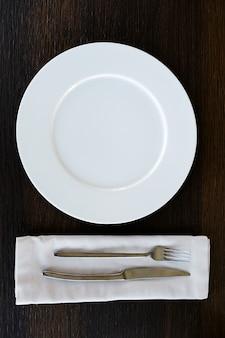 Metalowy nóż i widelec na lekkiej serwetce. urządzenia do żywności. obok pustej płyty.