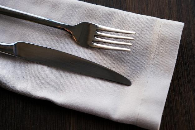 Metalowy nóż i widelec na lekkiej serwetce. urządzenia do żywności.