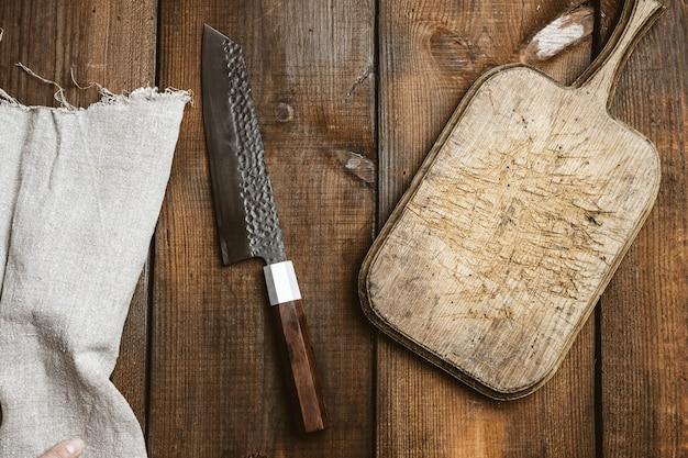 Metalowy nóż kuchenny i drewniana deska do krojenia na stole z brązowych desek, widok z góry