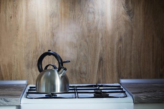 Metalowy srebrny nowoczesny czajnik na kuchence gazowej w kuchni