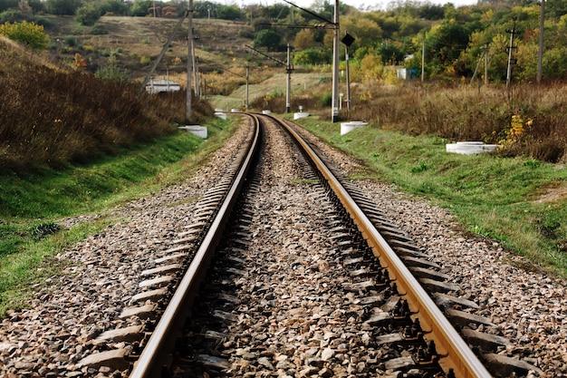 Metalowy stary tor kolejowy na tle przyrody z kamieniami, trawą i drzewami, ukraiński sposób transportu