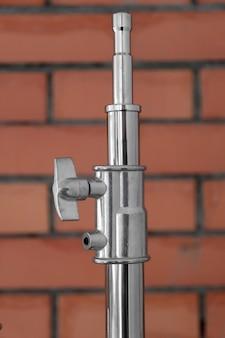 Metalowy statyw oświetleniowy z mechanizmem mocującym nad murem z czerwonej cegły