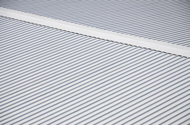 Metalowy szary dach z rytmicznymi równoległymi kierunkami reliefu