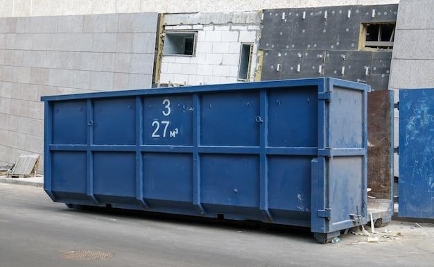 Metalowy trwały niebieski przemysłowy kosz na śmieci na zewnątrz na placu budowy. duży kosz na odpady domowe lub przemysłowe. kupa odpadów.