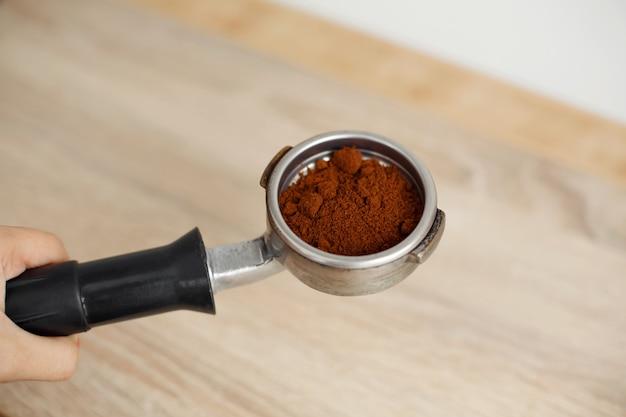 Metalowy uchwyt do ekspresu do kawy z mieloną kawą wewnątrz leży na drewnianym stole