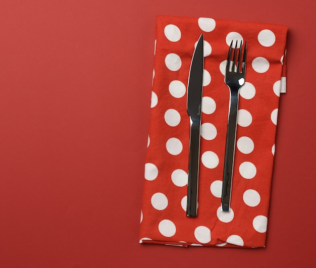 Metalowy widelec i nóż, czerwone tło, miejsce na napis, widok z góry