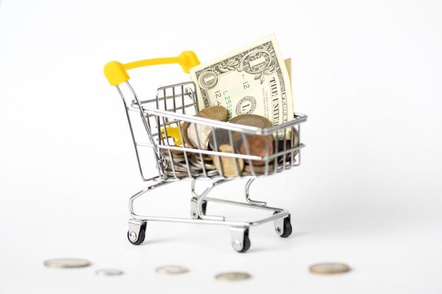 Metalowy wózek supermarketu pełen pieniędzy. kursy wymiany. monety, dolar.