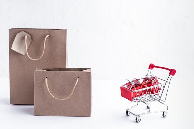 Metalowy wózek z prezentami i torby na zakupy na białym