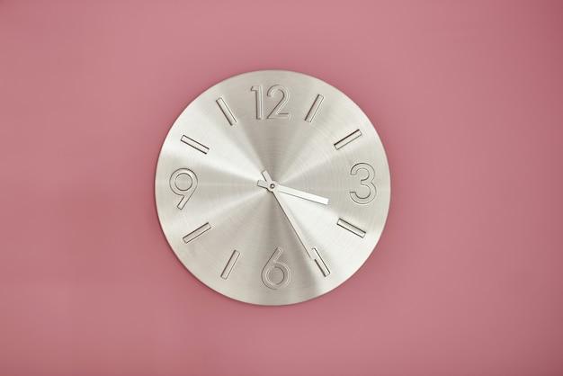 Metalowy zegar na ścianie pomalowanej na różowo