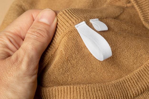 Metka na ubrania na wełnianym brązowym swetrze