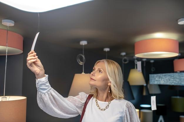 Metka z ceną lampy wiszącej. kobieta sukcesu z biżuterią na szyi, patrząc na ceną żyrandola, podnosząc rękę, zaciekawiona.