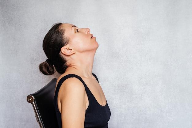 Metoda mckenzie ćwiczenie łagodzące ból karku kobieta delikatnie kręci głową podczas robienia bólu karku...