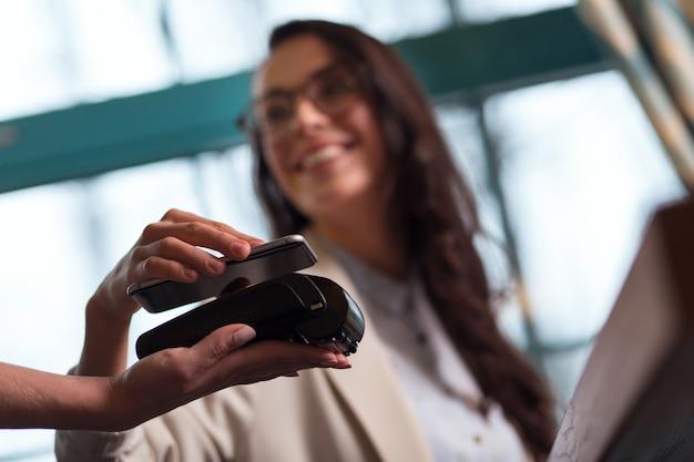 Metoda płatności. selektywne skupienie się terminala na płatności, które prowadzi kobieca ręka i elegancka kobieta za pomocą smartfona z systemem nfc