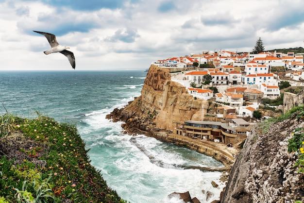 Mewa przelatująca nad typową rybacką wioską azenhas do mar w sintra w portugalii.