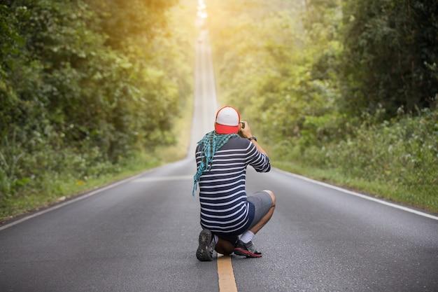 Mężczyzn fotograf trzyma aparat w dziczy i na drodze do zrobienia zdjęcia