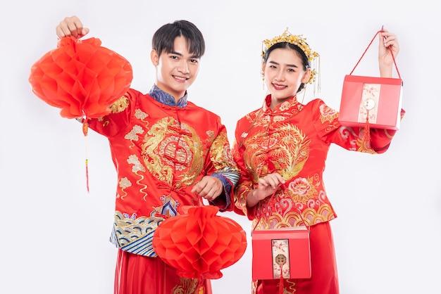 Mężczyzn i kobiet noszących cheongsam stojący trzymając czerwoną torbę i latarnię o strukturze plastra miodu
