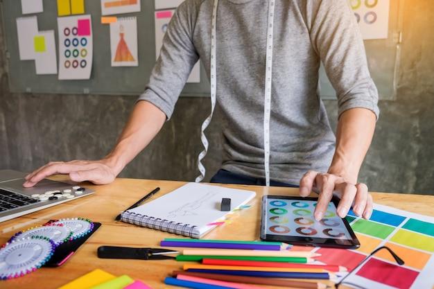 Mężczyzn pracujących jako projektant mody wybierając na wykres kolorów dla ubrania w cyfrowym tablecie w miejscu pracy studio.