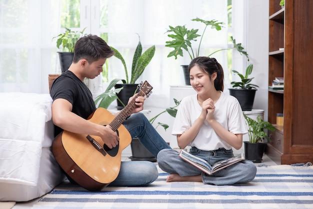 Mężczyzn siedzących na gitarze i kobiet trzymających książki i śpiewających.