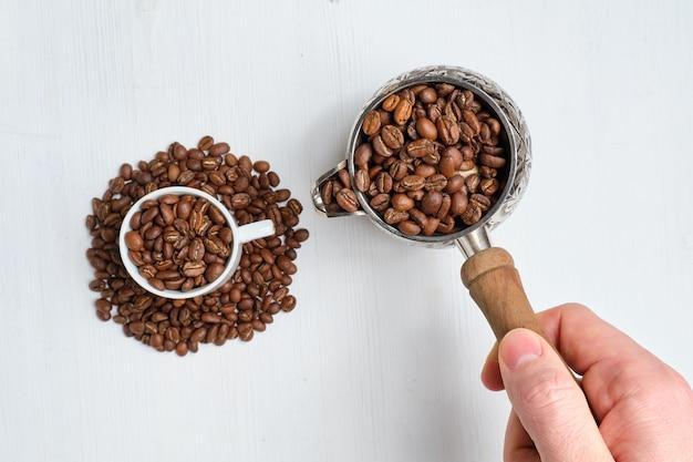 Mężczyzna abstrakcyjnie nalewa kawę z turka do filiżanki ziaren.