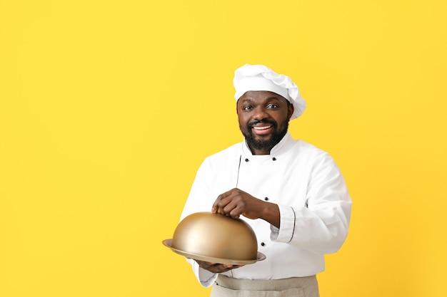 Mężczyzna african-american kucharz z tacą i cloche na kolor