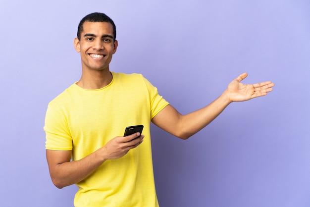 Mężczyzna afroamerykanów nad izolowanym fioletowy ściany za pomocą telefonu komórkowego wyciągając ręce na bok za zaproszenie