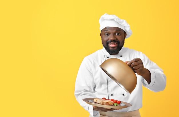 Mężczyzna afroamerykański szef kuchni ze smacznym daniem na żółto