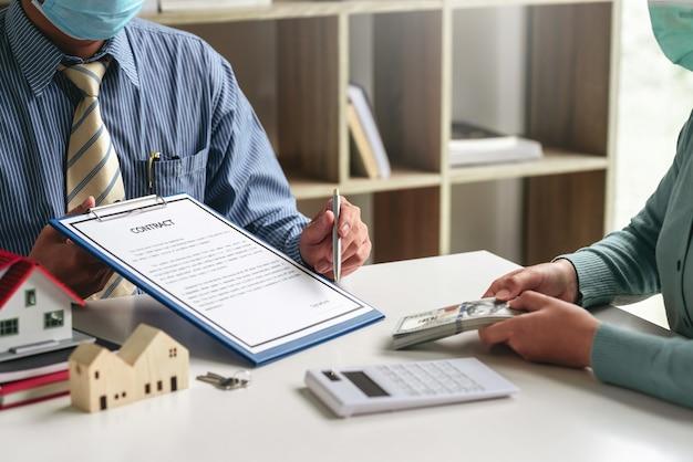 Mężczyzna agent nieruchomości trzymający pióro wskazujące na podpisywanie dokumentów klienta trzymającego koncepcję handlu domem w biurze