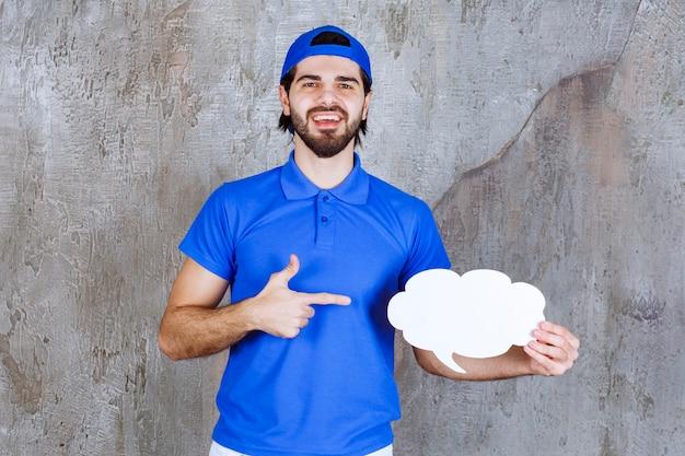 Mężczyzna agent usług w niebieskim mundurze, trzymający pustą tablicę informacyjną w kształcie chmury