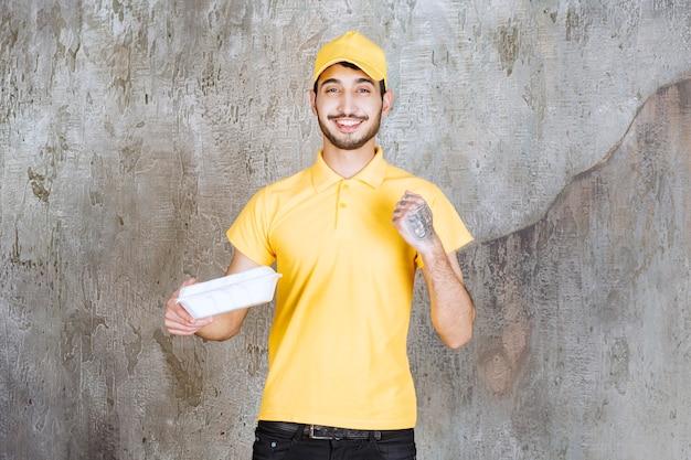 Mężczyzna agent usług w żółtym mundurze trzyma białe pudełko na wynos i pokazuje pięść.