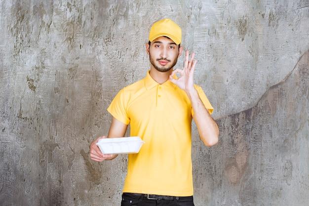 Mężczyzna agent usług w żółtym mundurze trzyma białe pudełko na wynos i pokazuje znak przyjemności.