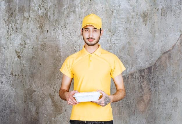 Mężczyzna agent usług w żółtym mundurze, trzymający białe pudełko na wynos