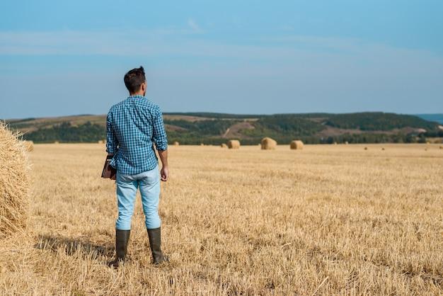 Mężczyzna agronom rolnik w dżinsach i koszuli stoi w polu po sianokosy, z tabletem patrząc w dal.