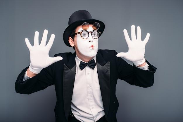 Mężczyzna aktor pantomimy zabawa wykonywania. mim w garniturze, rękawiczkach, okularach, masce do makijażu i czapce.