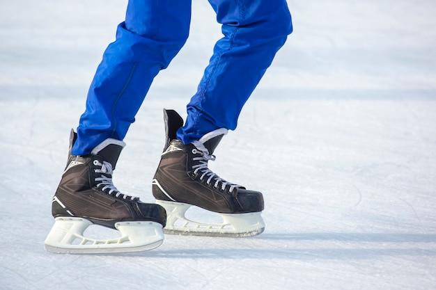 Mężczyzna aktywnie jeździ na łyżwach na lodowisku. hobby i sport. wakacje i zajęcia zimowe.