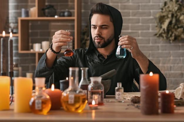 Mężczyzna alchemik robi eliksir w laboratorium