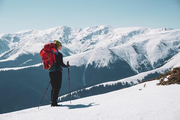 Mężczyzna alpinista, ciesząc się pokrytym śniegiem widokiem na góry ze szczytu
