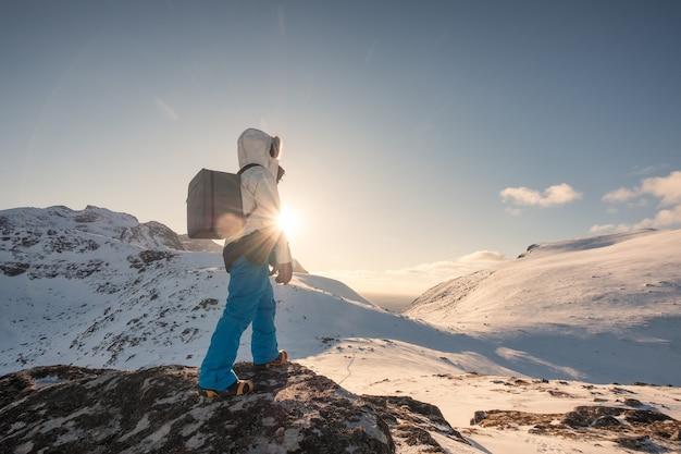 Mężczyzna alpinista wspina się na zaśnieżonej górze o zachodzie słońca