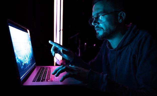 Mężczyzna analizujący dane finansowe z wykresów giełdowych na elektronicznej tablicy