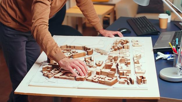 Mężczyzna architekt pracujący przy budowie nowego miasta. modele budowlane.