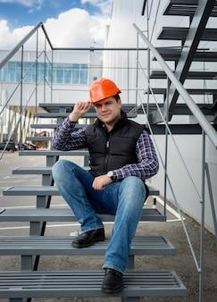 Mężczyzna architekt w czerwonym kasku siedzi na metalowych schodach w fabryce