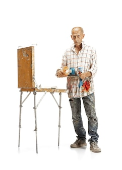 Mężczyzna artysta kaukaski, malarz w pracy na białym tle na białym studio