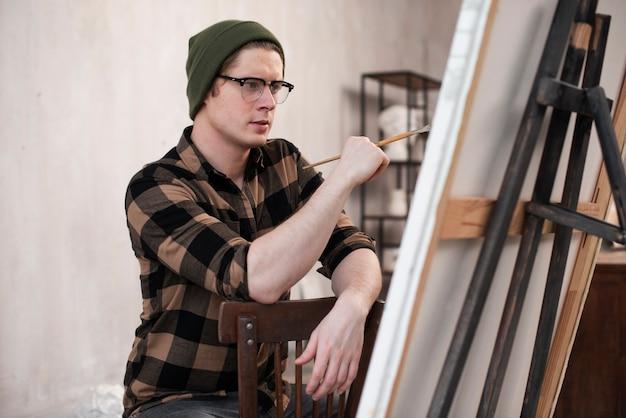 Mężczyzna artysta malujący na płótnie