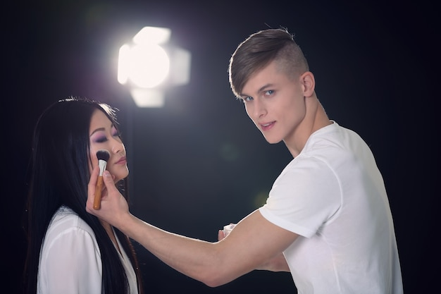Mężczyzna artysta robi makijaż dla modelu na ciemnym tle