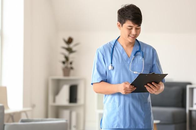 Mężczyzna asystent medyczny ze schowkiem w klinice