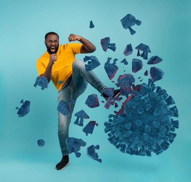Mężczyzna atakuje kopnięciem koronawirusa. niebieska ściana