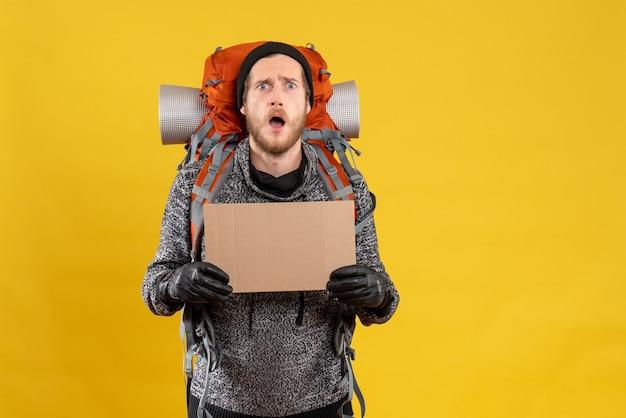 Mężczyzna autostopowicz w czarnym kapeluszu i plecaku trzymającym pusty karton