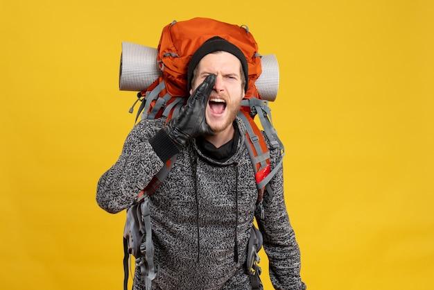 Mężczyzna autostopowicz w skórzanych rękawiczkach i krzyczącym plecaku