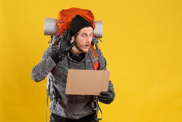 Mężczyzna autostopowicz w skórzanych rękawiczkach i plecak z pustym kartonem słuchający czegoś