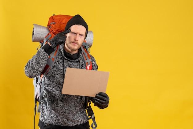Mężczyzna autostopowicz w skórzanych rękawiczkach i plecak z pustym kartonowym myśleniem